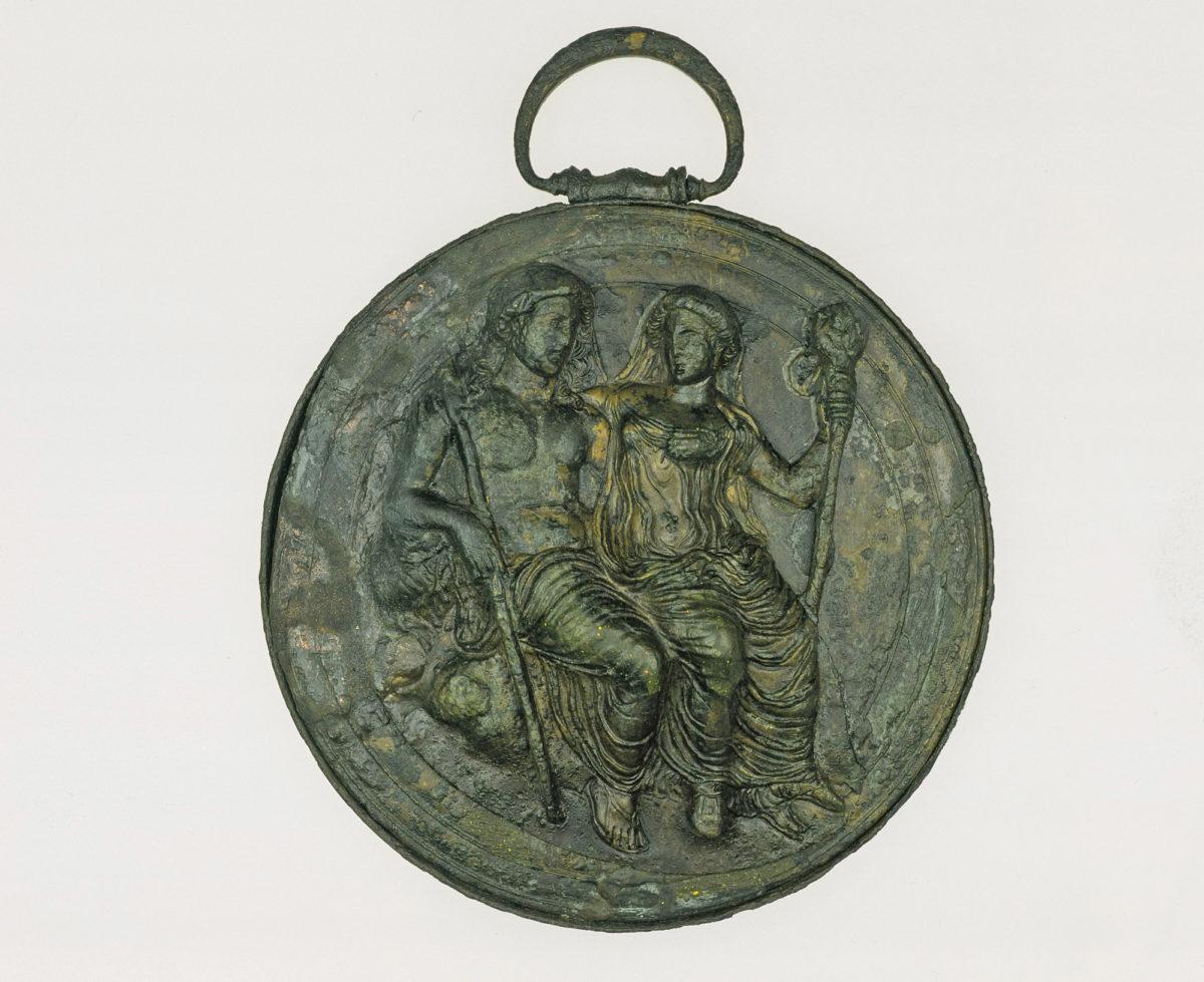 Πτυκτό κάτοπτρο με ανάγλυφη παράσταση Διονύσου και Aριάδνης στο κάλυμμα. Στην περιφέρεια σώζεται η λαβή για την ανάρτηση. Γύρω στο 330 π.X. Bόνιτσα Aιτωλοακαρνανίας (© Εθνικό Αρχαιολογικό Μουσείο/ TAΠΑ).