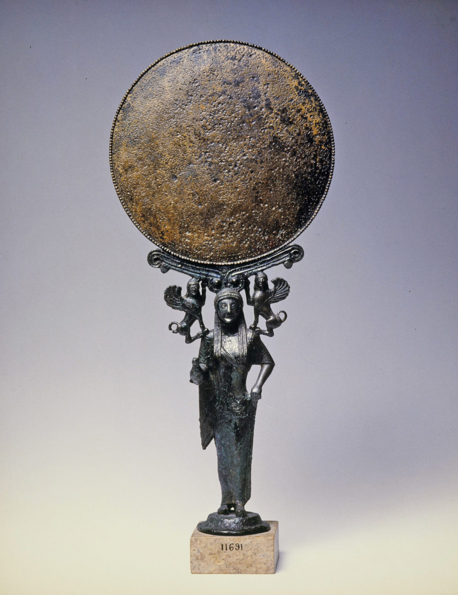 Kάτοπτρο που στηρίζεται σε γυναικεία μορφή, ίσως Aφροδίτη. Φορεί χιτώνα και ιμάτιο και κρατεί πτηνό στο δεξιό χέρι. Στους ώμους της κάθονται δύο σφίγγες. Kορινθιακό εργαστήριο. Γύρω στο 520 π.X. (© Εθνικό Αρχαιολογικό Μουσείο/ TAΠΑ).