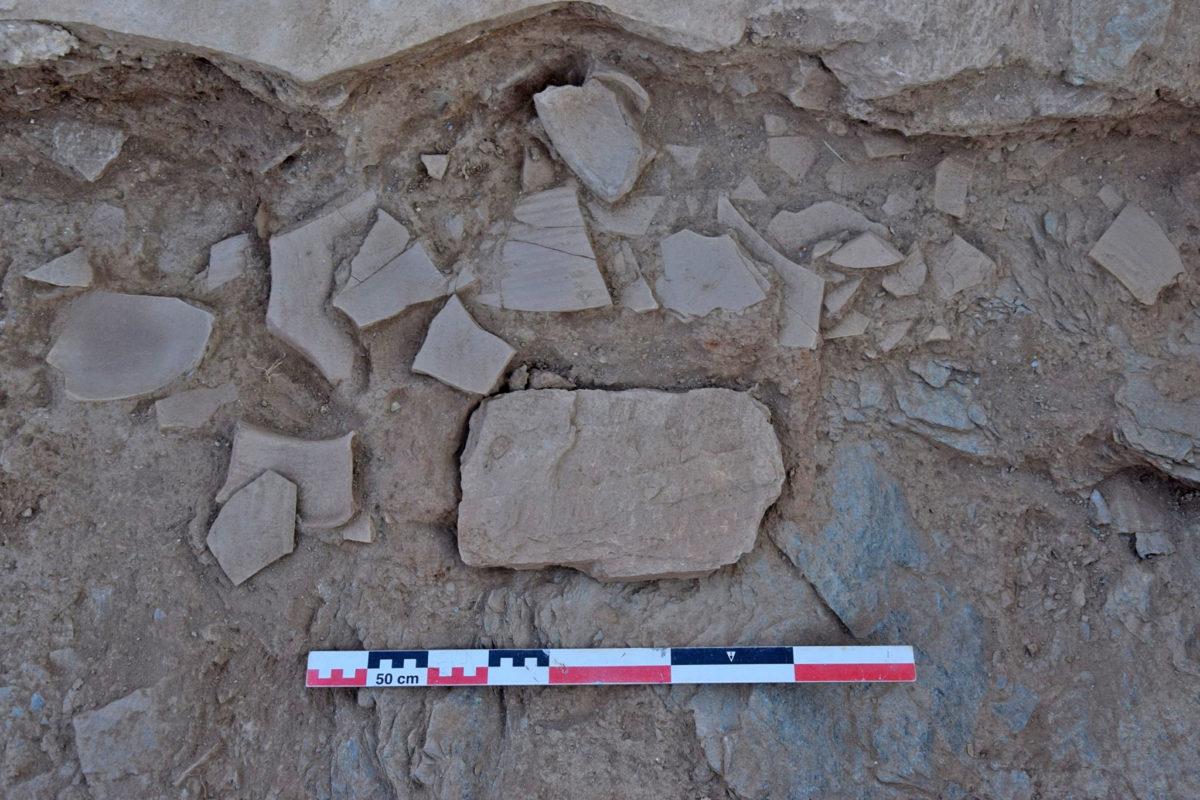 Η καλυπτήρια πλάκα της θήκης του εγκαινίου και το στρώμα με τα θραύσματα πρωτοβυζαντινής κεραμικής (φωτ.: ΥΠΠΟΑ).