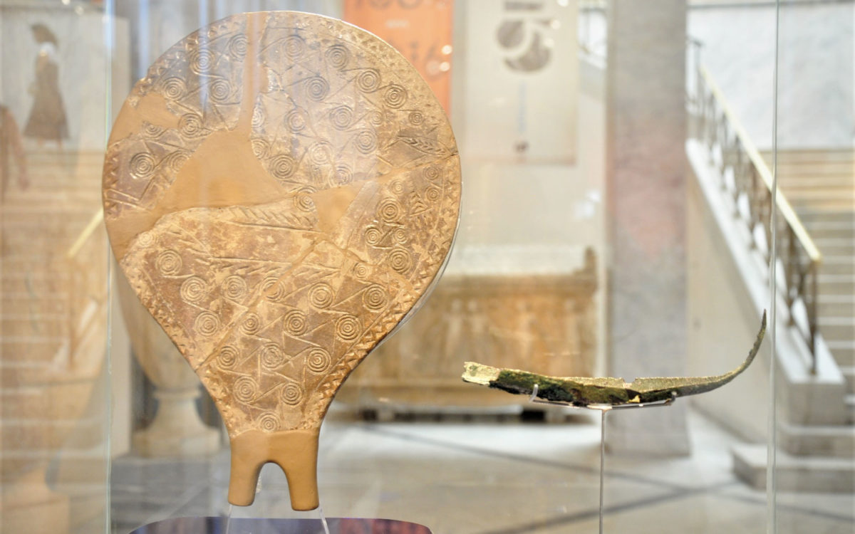 Πήλινο τηγανόσχημο σκεύος από τη Χαλανδριανή Σύρου, 2800-2300 π.Χ. (Πρωτοκυκλαδική ΙΙ περίοδος) (ΕΑΜ Π 6177.1 © TAΠΑ/Εθνικό Αρχαιολογικό Μουσείο) και χάλκινο ομοίωμα λέμβου από την Κέα, 16ος αι. π.Χ. (Υστεροκυκλαδική Ι περίοδος) (ΕΑΜ Π 21532 © TAΠΑ/Εθνικό Αρχαιολογικό Μουσείο).