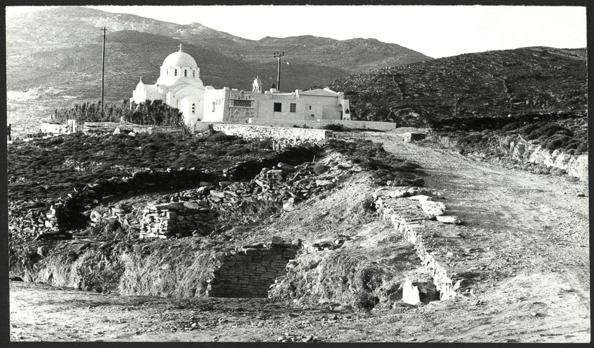 Άποψη της ανασκαφής στην Αγία Θέκλα, στην Τήνο, το 1979. Διακρίνονται τα υπολείμματα του θολωτού τάφου (κάτω) και η ομώνυμη εκκλησία (πάνω). © Αρχείο της εν Αθήναις Αρχαιολογικής Εταιρείας.