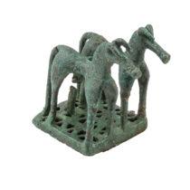 Χάλκινο αναθηματικό ειδώλιο «δίδυμων» ίππων σε ενιαία διάτρητη βάση. Το σώμα των αλόγων και οι πλάγιες όψεις της βάσης κοσμούνται με εγχάρακτους κύκλους. Τέλη 8ου αι. π.Χ. Αρχαιολογικό Μουσείο Θέρμου.