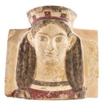Ακροκέραμο με γυναικεία προτομή, που φορά πόλο στην κεφαλή. Προέρχεται από την πρώιμη κλασική στέγη (470–460 π.Χ.) του ναού του Απόλλωνος. Αρχαιολογικό Μουσείο Θέρμου.