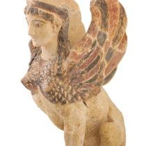 Γωνιακό ακρωτήριο με τη μορφή καθιστής Σφίγγας. Προέρχεται από την πρώιμη κλασική στέγη (470–460 π.Χ.) του ναού του Απόλλωνος. Αρχαιολογικό Μουσείο Θέρμου.