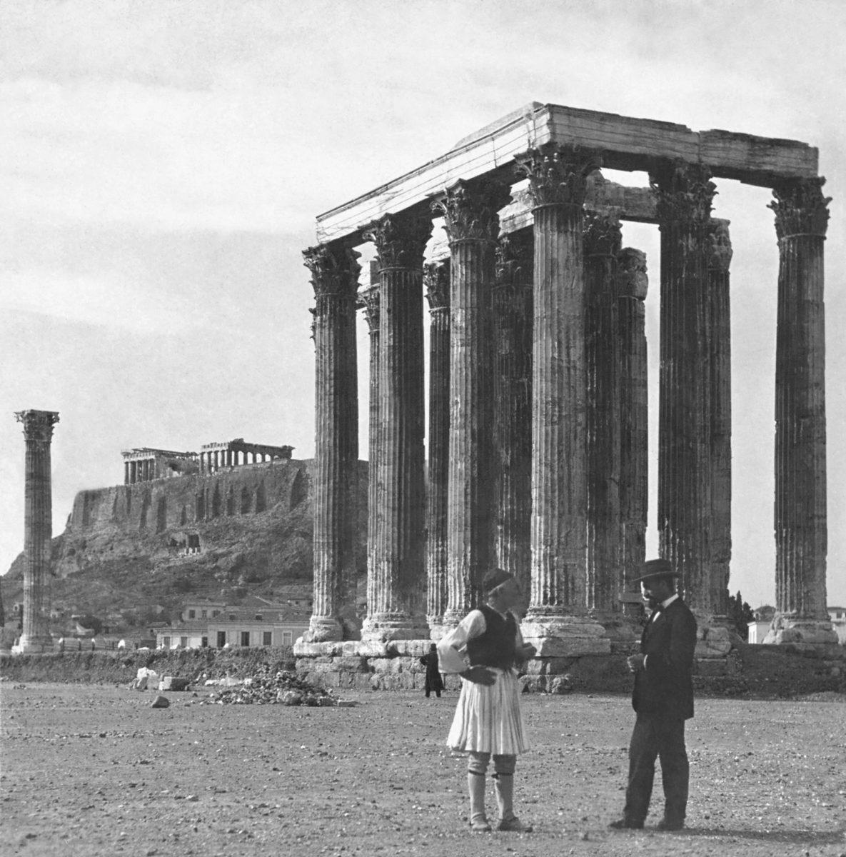 Ένας τσολιάς και ένας αστός συζητούν μπροστά στους στύλους του Ολυμπίου Διός. Τέλη 19ου-αρχές 20ου αιώνα. Άγνωστος φωτογράφος. Ευγενική παραχώρηση: Library of Congress.