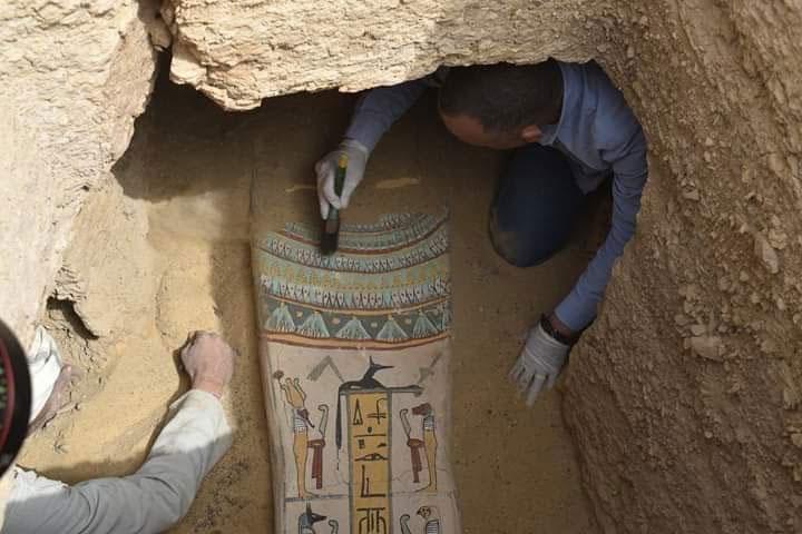 Ξύλινη σαρκοφάγος με ιερογλυφικό κείμενο σε κίτρινο φόντο, κατά τη διάρκεια της ανασκαφής.