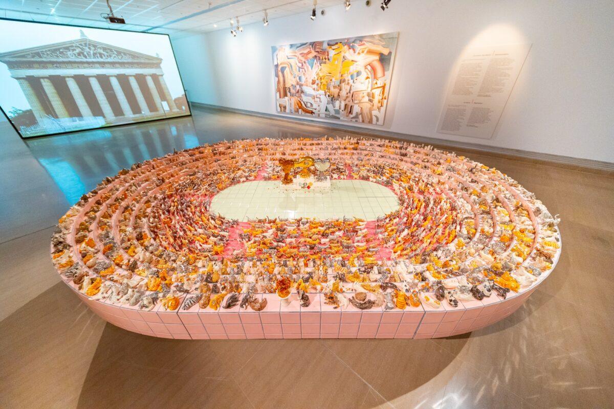 Άποψη της περιοδικής έκθεσης όπου σε πρώτο πλάνο διακρίνεται το έργο «Τελετή έναρξης των Ολυμπιακών Αγώνων για γάτες» του Νομπουάκι Τακεκάβα (2019), στον τοίχο το έργο «Επαναπατρισμός» του Κέι Ιμάτζου (2015) και στο βάθος η βιντεοεγκατάσταση «Αυθεντικότητα» του Γιου Αράκι (2016) με άμεση αναφορά στον Παρθενώνα (© ΥΠΠΟΑ/ΒΧΜ).