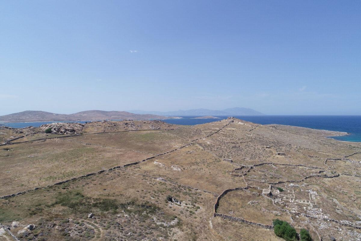 Η ελληνιστική νεκρόπολη της Δήλου στη Ρήνεια, ο πυραμιδοειδής λόφος Χωμασοβούνι όπου πιθανολογείται η θέση του Αρτεμισίου εν νήσω των δηλιακών επιγραφών, και αριστερά αρχαία αγροικία δίπλα σε νεότερη. Στο βάθος, το βόρειο τμήμα της Ρήνειας και στον ορίζοντα η Τήνος (φωτ.: ΥΠΠΟΑ).