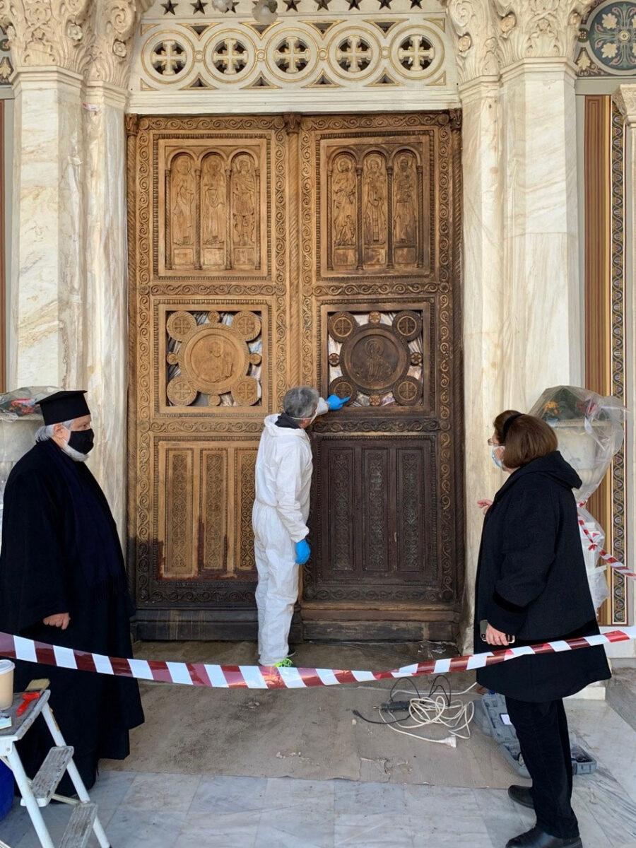 Η περίτεχνη ξύλινη κεντρική πύλη του Μητροπολιτικού Ναού Αθηνών κοσμείταιαπό ολόσωμες μορφές αγίων και ανάγλυφα διακοσμητικά μετάλλια (φωτ.: ΥΠΠΟΑ).