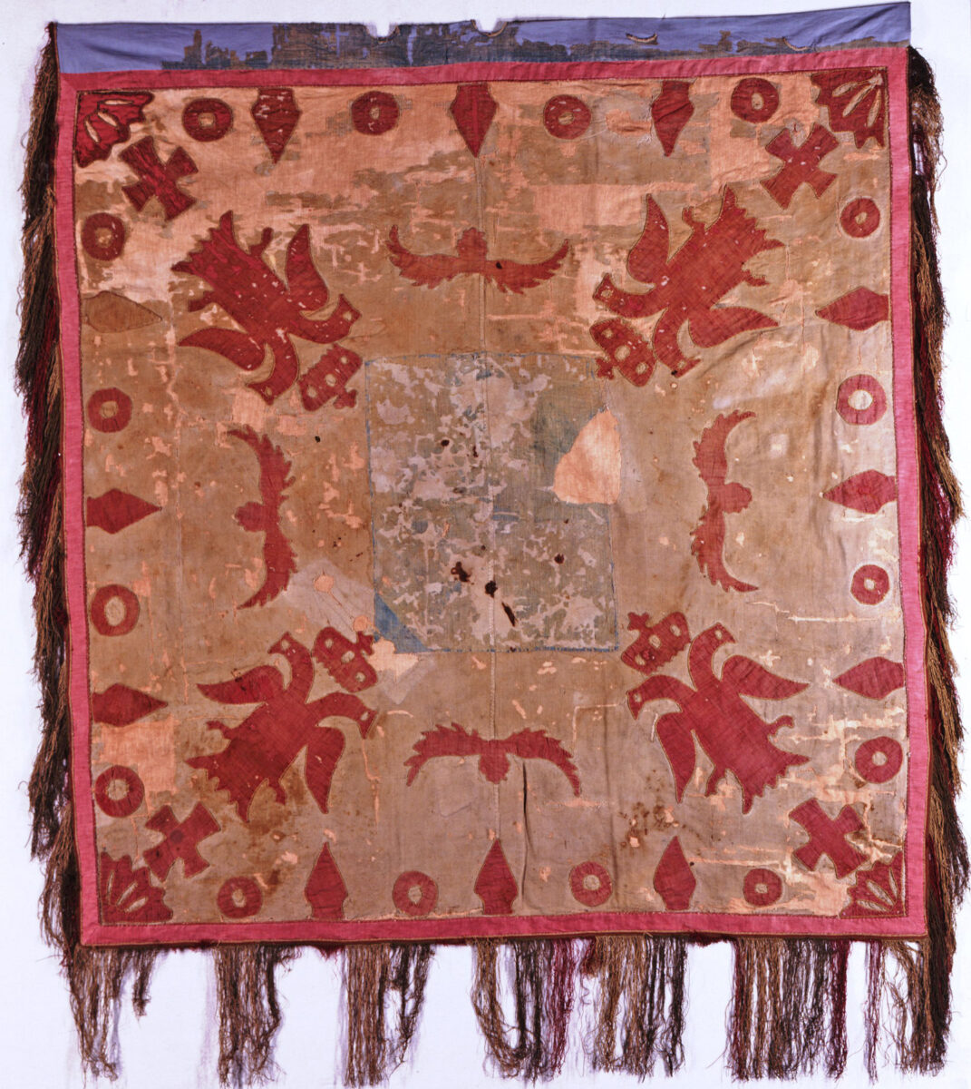 Σημαία Ηπειρωτών που υψώθηκε στον Αγώνα του 1821. Βαμβακερό υφαντό (ΕΙΜ 2744). Φέρει σύμβολα της Βυζαντινής Αυτοκρατορίας: πορφυροί εστεμμένοι αετοί, δικέφαλοι, σταυροί. Στο κέντρο, φθαρμένος πια, δεσπόζει γαλάζιος σταυρός σε λευκό πλαίσιο. © ΙΕΕΕ-ΕΙΜ.