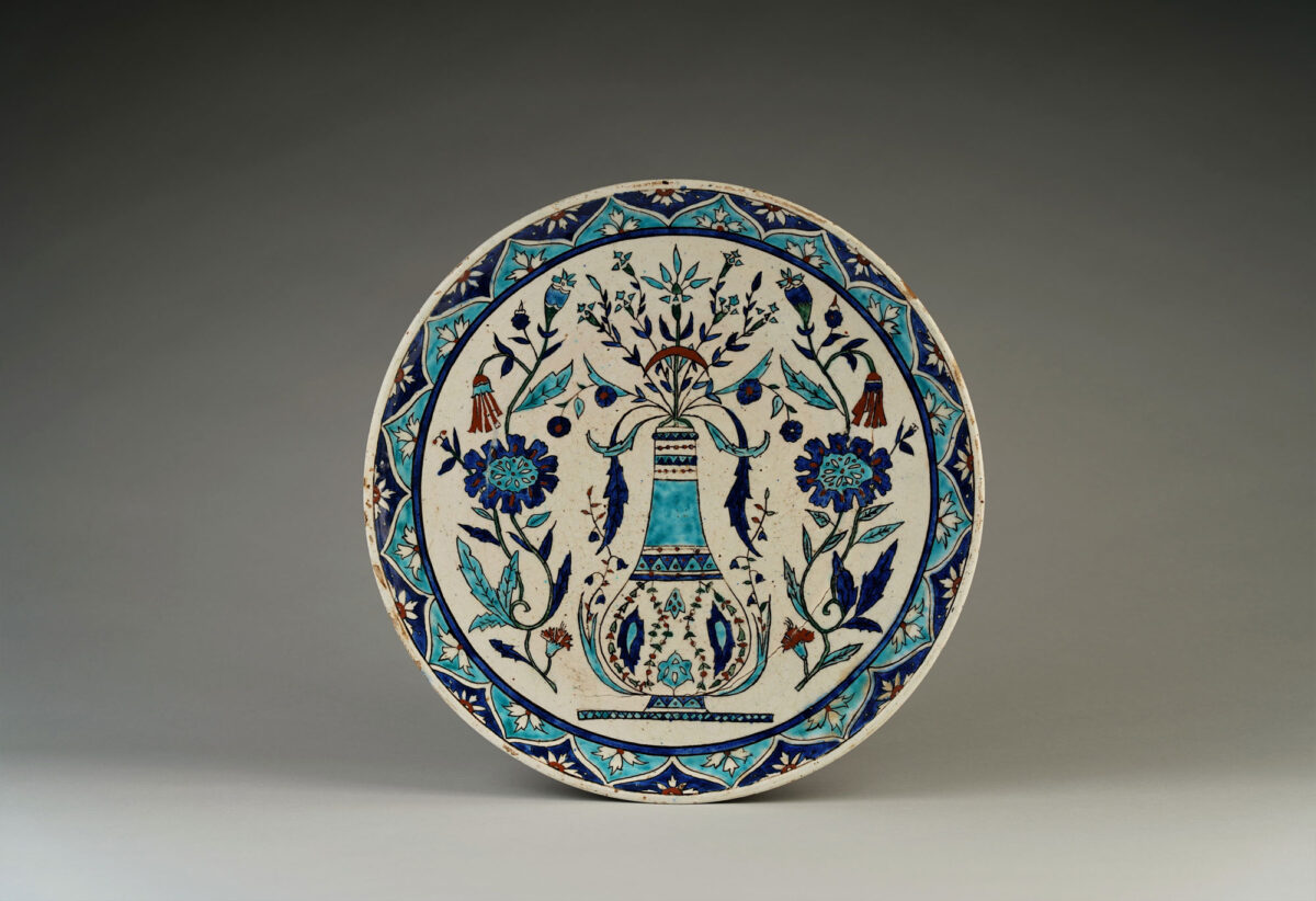 Πιάτο με παράσταση κανατιού για νερό πλαισιωμένη από φυτικά και άνθινα μοτίβα. Κιουτάχεια, τέλη 19ου – αρχές 20ού αιώνα. Διάμετρος: 37 εκ. Ιδιωτική συλλογή.