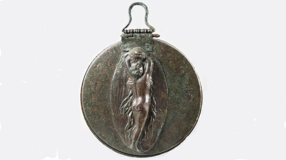 Χάλκινο πτυκτό κάτοπτρο με ανάγλυφη παράσταση απαγωγής του Γανυμήδη από τον Δία μεταμορφωμένο σε αετό. Από τη Μάκιστο, «Πετροπήγαδα». Ελληνιστική περίοδος. Αρχαιολογικό Μουσείο Πύργου Μ 2441. © ΥΠΠΟΑ/Εφορεία Αρχαιοτήτων Ηλείας/ΟΔΑΠ. Φωτ.: Ειρήνη Μίαρη.