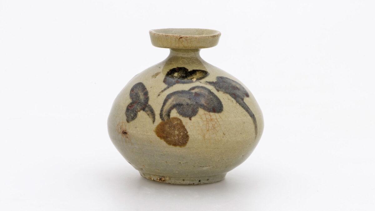 Αγγείο λαδιού («κιρουμπγιόνγκ»). Λιθοκέραμος με γραπτή διακόσμηση φύλλων παιώνιας σε χρώμα καφέ σιδήρου κάτω από πράσινη εφυάλωση. Κορέα. Δυναστεία Κόρυο (918-1392), 12ος αι. Διάμ. 6,8 εκ. Μουσείο Μπενάκη 2420. Δωρεά Γεωργίου Ευμορφόπουλου.
